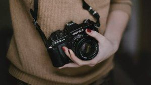 Person holding an old analog camera